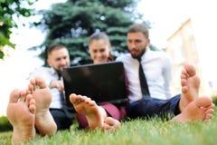 amis dans des vêtements d'affaires et se reposer nu-pieds sur l'herbe tenant l'ordinateur portable dans des mains Photographie stock