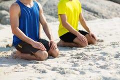 Amis dans l'habillement de sports se mettant à genoux sur le rivage à la plage Photos stock