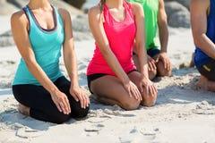 Amis dans l'habillement de sports se mettant à genoux sur le rivage Photo libre de droits