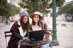 Amis dans l'ordinateur portable sur la rue Photos stock
