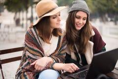 Amis dans l'ordinateur portable sur la rue Photographie stock