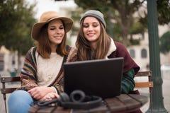 Amis dans l'ordinateur portable sur la rue Image libre de droits