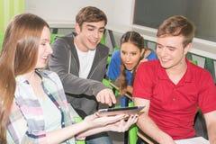 Amis dans l'université avec un smartphone Photos libres de droits