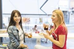 Amis dans la barre, deux filles buvant dans le restaurant Photographie stock