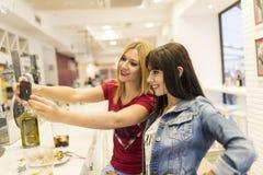 Amis dans la barre, deux filles buvant dans le restaurant Image stock