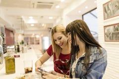 Amis dans la barre, deux filles buvant dans le restaurant Photographie stock libre de droits