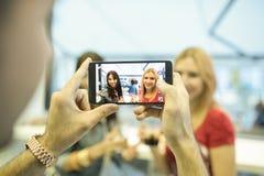 Amis dans la barre prenant des photos avec des smartphones Photos libres de droits