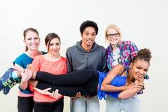 Amis dans la femme de transport de classe de danse sur des mains Photo stock