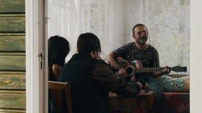 Amis dans la maison de campagne Guitare de jeu d'homme Homme avec le cognac rouge de boissons de nez banque de vidéos