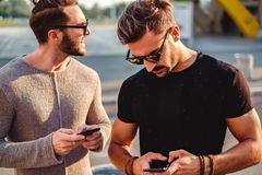 Amis dans la rue regardant le téléphone pour l'emplacement Images stock