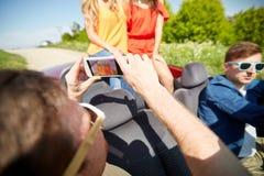 Amis dans la voiture photographiant par le smartphone Image libre de droits