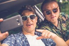Amis dans la voiture se préparant au voyage de vacances de route et prenant l'autoportrait à l'aide du téléphone portable Photographie stock