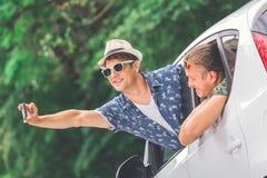 Amis dans la voiture se préparant au voyage de vacances de route et prenant l'autoportrait à l'aide du téléphone portable Photos libres de droits