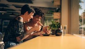 Amis dans le café regardant le téléphone portable Photographie stock libre de droits