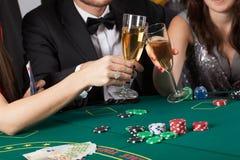 Amis dans le casino soulevant des verres Images libres de droits
