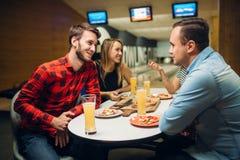Amis dans le club de bowling, panneau de jeu sur le fond photos stock