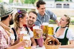 Amis dans le jardin bavarois de bière buvant en été Image stock