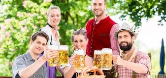 Amis dans le jardin bavarois de bière buvant en été Photographie stock libre de droits