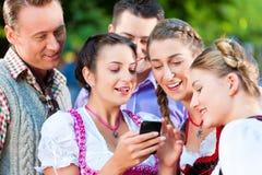 Amis dans le jardin de bière avec le smartphone Photo libre de droits