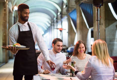 Amis dans le restaurant et serveur noir Images libres de droits
