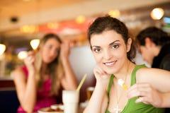 Amis dans le restaurant mangeant des aliments de préparation rapide Photographie stock libre de droits