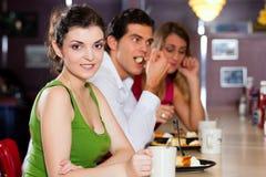 Amis dans le restaurant mangeant et buvant Photographie stock