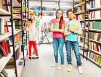 Amis dans le support de bibliothèque ainsi que des livres Photo stock