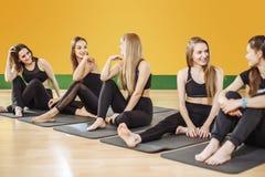 Amis dans les vêtements de sport parlant et riant ensemble tout en se reposant sur le plancher d'un gymnase après une séance d'en Photographie stock libre de droits
