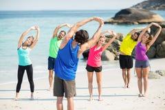 Amis dans les vêtements de sport s'étendant tout en se tenant sur le rivage Photo libre de droits