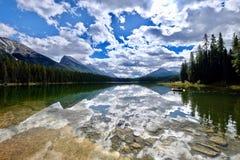 Amis dans un bateau sur le beau lac Réflexion de montagnes et de nuages dans l'eau calme Photo stock