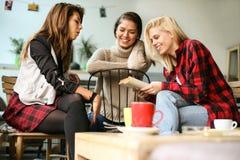 Amis dans un café Jeunes femmes d'arbre Photographie stock