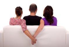 Amis dans un divan, avec deux filles données des mains Photo stock