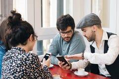 Amis dans une barre utilisant des mobiles Image libre de droits