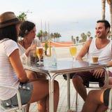 Amis dans une bière potable de barre de plage Photographie stock libre de droits