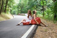Amis dans une route faisant de l'auto-stop avec la caisse de guitare Images libres de droits