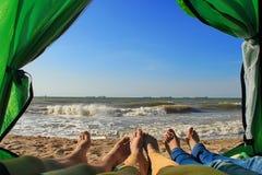 Amis dans une tente au bord de la mer Image stock