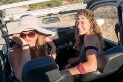 Amis dans une voiture au coucher du soleil Photos stock