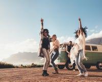 Amis dansant et ayant l'amusement sur le voyage par la route Photo libre de droits