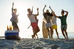 Amis dansant sur le rivage à la plage Photographie stock libre de droits