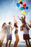 Amis dansant sur le sable avec le ballon Image stock