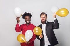 Amis de bonheur célébrant l'anniversaire, tenant l'or et le blanc a Image stock