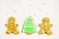 Amis de bonhommes en pain d'épice à l'arbre de Noël sur un blanc en bois Images libres de droits