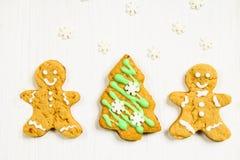 Amis de bonhommes en pain d'épice à l'arbre de Noël sur un blanc en bois Photos stock