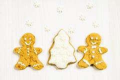 Amis de bonhommes en pain d'épice à l'arbre de Noël sur un blanc en bois Photographie stock