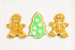Amis de bonhommes en pain d'épice à l'arbre de Noël sur un blanc en bois Image libre de droits