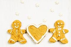 Amis de bonhommes en pain d'épice près du coeur sur une table en bois blanche Image stock