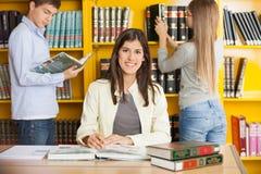 Amis de With Books While d'étudiant à l'arrière-plan à Image libre de droits