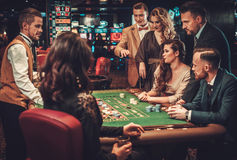 Amis de classe aristocratique jouant dans un casino Photos stock