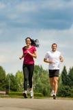 Amis de couples courant une course en parc Photographie stock