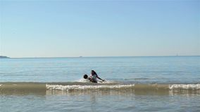 Amis de couples tenant des mains et ayant l'amusement Ils ont l'aspect caucasien La mer avec des vagues est sur le fond banque de vidéos